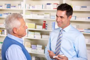 smiling pharmacist serving senior man in a pharmacy