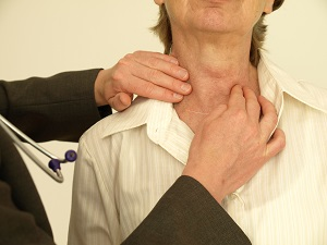Doctor checking senior woman's thyroid gland